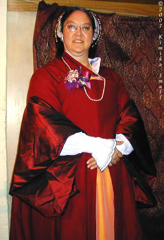 A photo of me, Kimiko, wearing my red wool & silk Tudor gown c.1530s, topped by my white silk French hood.